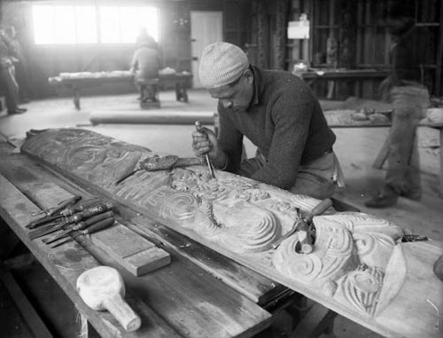 Pineāmine Taiapa working on a wood carving with a chisel