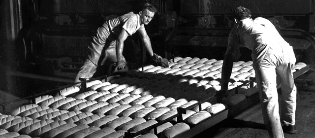 Workers lift trays of bread in a bakery