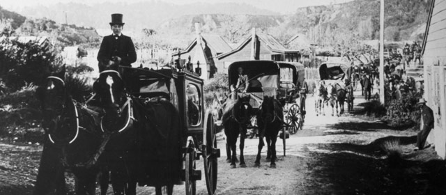 A funeral cortège moves through Hokitika, 1914