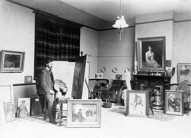 Sydney Lough Thompson at his easel surrounded by his works, probably after 1905